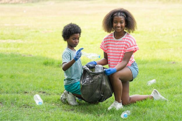 Bambini afroamericani che raccolgono volontariamente bottiglie di plastica in un sacco della spazzatura nero al parco, aiutano l'ambiente di beneficenza della raccolta dei rifiuti