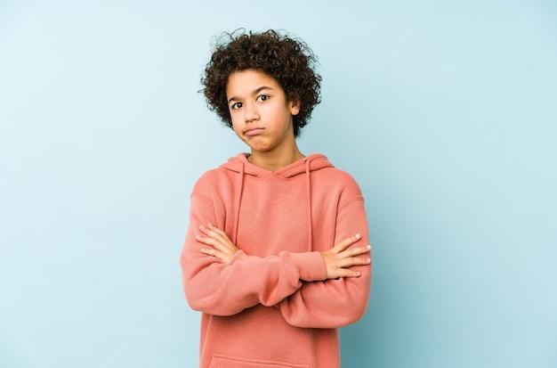 Ragazzino afroamericano isolato infelice con espressione sarcastica.