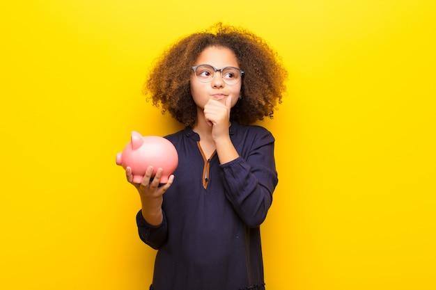 Bambina afroamericana contro la parete piana che tiene un porcellino salvadanaio