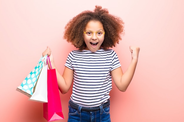 Bambina afroamericana contro la parete piana con i sacchetti della spesa