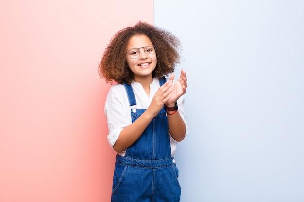 Bambina afroamericana sentirsi felici e di successo, sorridendo e battendo le mani, dicendo congratulazioni con un applauso contro la parete piatta