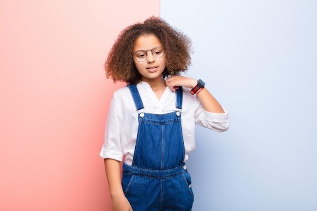 Bambina afroamericana che si sente stressata, ansiosa, stanca e frustrata, tira il collo della camicia, sembra frustrata dal problema contro la parete piatta