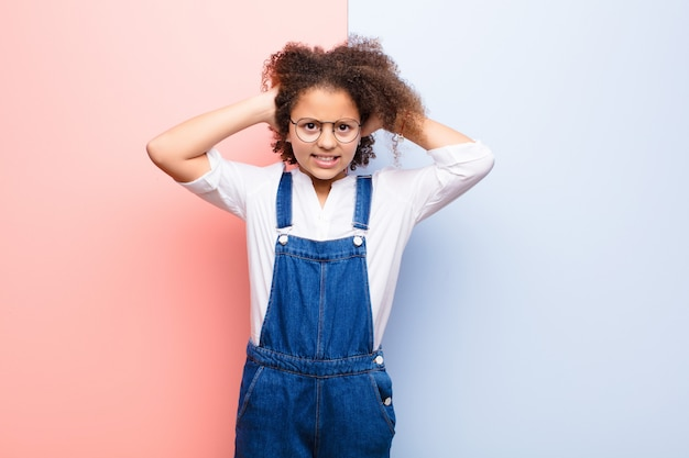 Bambina afroamericana che si sente stressata, preoccupata, ansiosa o spaventata, con le mani sulla testa, in preda al panico per errore contro il muro piatto