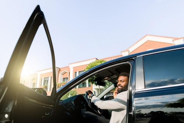 Uomo d'affari del capo maschio dell'afroamericano che per mezzo dello smartphone per effettuare la chiamata durante mentre sedendosi in automobile di lusso con la porta aperta, telefono serio concentrato uomo serio al partner. vista laterale