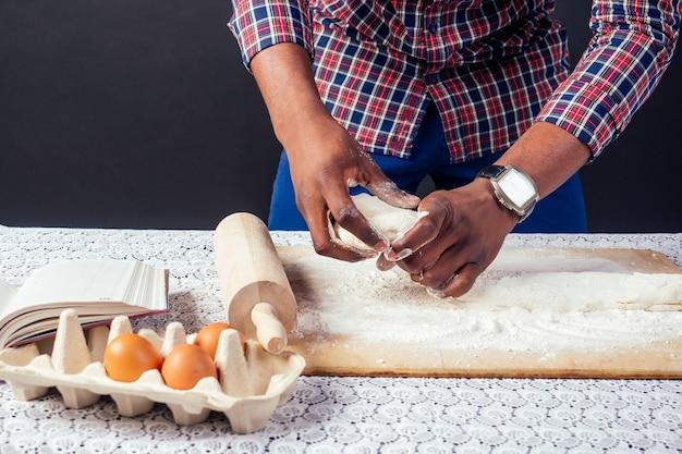 Chef cuoco maschio afroamericano si vanta di mani di pasticceria nella cottura della farina. le mani dell'uomo fogli di pasta con il mattarello cuoce la torta, le uova e il libro di ricette sul tavolo. cottura casalinga.