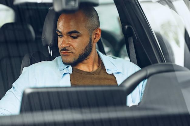 Driver maschio afroamericano che si siede in una macchina