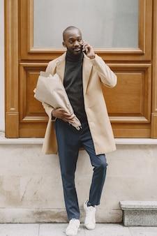 Uomo afroamericano in una città. ragazzo che tiene il mazzo di fiori. maschio in un cappotto marrone.