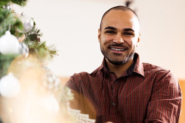 Uomo afroamericano che decora l'albero di natale a casa
