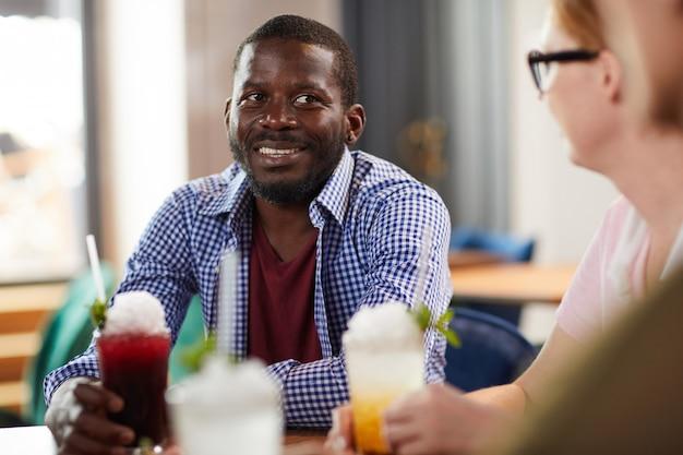 Uomo afroamericano che gode delle bevande con gli amici
