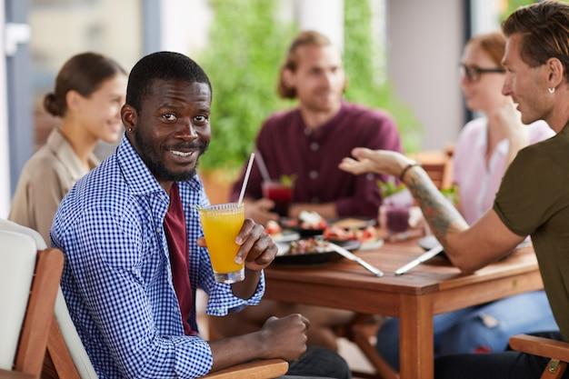 Uomo afroamericano che gode del pranzo con gli amici in caffè