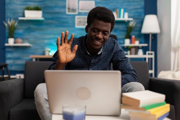 Uomo afroamericano che saluta il collega remoto durante la conferenza di riunione di videochiamata online discutendo il webinar di gestione utilizzando la piattaforma scolastica sul computer portatile. telelavoro in videoconferenza di ateneo