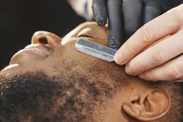 Uomo afroamericano. ragazzo seduto su una sedia. il barbiere lavora con la barba.