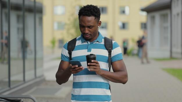 Uomo afroamericano che fa una passeggiata in città godendosi il suo gustoso caffè digitando messaggi sul suo smartphone e bevendo caffè caldo