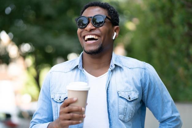 Uomo afroamericano che tiene una tazza di caffè mentre levandosi in piedi all'aperto sulla strada