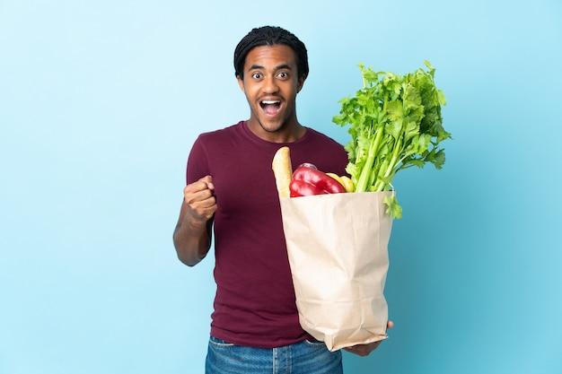 Uomo afroamericano che tiene un sacchetto della spesa della drogheria sull'azzurro che celebra una vittoria nella posizione del vincitore