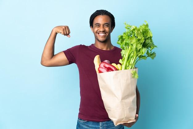 Uomo afroamericano che tiene un sacchetto della spesa della drogheria sull'azzurro che fa forte gesto