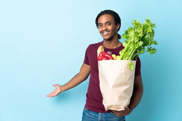 Uomo afroamericano che tiene un sacchetto della spesa della drogheria sulle mani estese blu al lato per invitare a venire