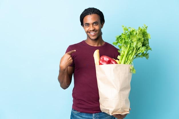 L'uomo afroamericano che tiene un sacchetto della spesa della drogheria sull'azzurro che dà i pollici aumenta il gesto