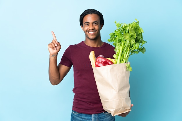 Uomo afroamericano che tiene un sacchetto della spesa della drogheria sull'azzurro che indica su una grande idea