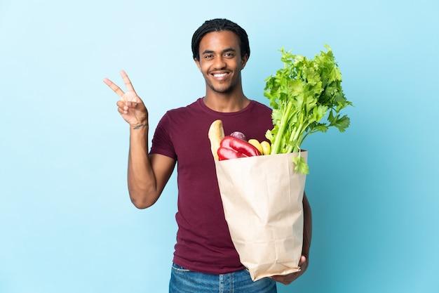 Uomo afroamericano che tiene un sacchetto della spesa della drogheria sull'azzurro che sorride e che mostra il segno di vittoria
