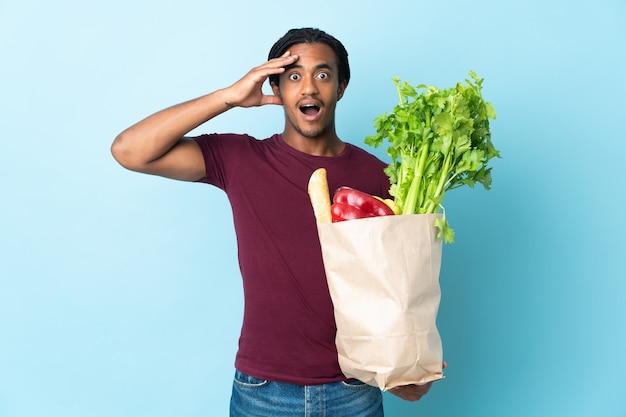 Uomo afroamericano che tiene un sacchetto della spesa della drogheria sull'azzurro con l'espressione di sorpresa