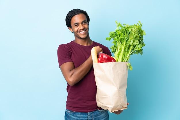 Uomo afroamericano che tiene un sacchetto della spesa della drogheria isolato su priorità bassa blu che celebra una vittoria