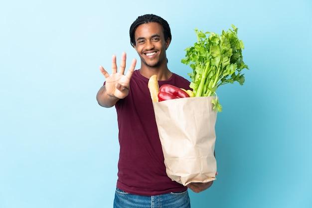 Uomo afroamericano che tiene un sacchetto della spesa isolato su priorità bassa blu felice e contando quattro con le dita