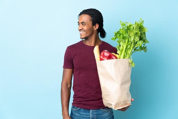 Uomo afroamericano che tiene un sacchetto della spesa della drogheria isolato su fondo blu che osserva lato