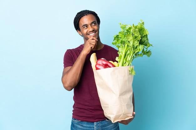 Uomo afroamericano che tiene un sacchetto della spesa della drogheria isolato su priorità bassa blu e che osserva in su