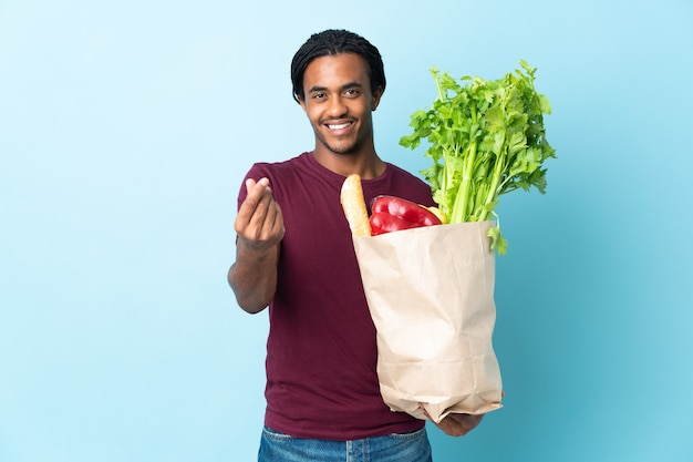 Uomo afroamericano che tiene un sacchetto della spesa della drogheria isolato su priorità bassa blu che fa gesto dei soldi