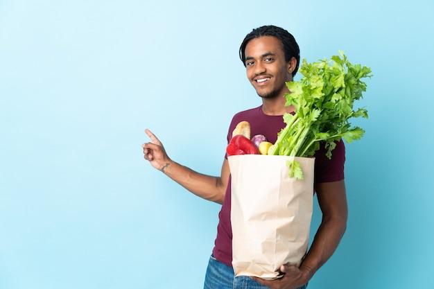 Uomo afroamericano che tiene una borsa della spesa della drogheria isolata su fondo blu che indica indietro