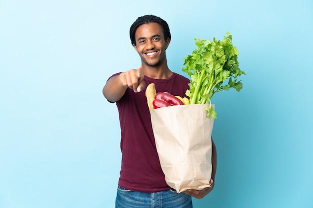 Uomo afroamericano che tiene un sacchetto della spesa della drogheria isolato su priorità bassa blu che indica davanti con l'espressione felice