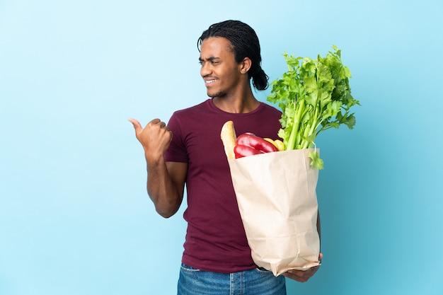 Uomo afroamericano che tiene un sacchetto della spesa della drogheria isolato su priorità bassa blu che indica al lato per presentare un prodotto