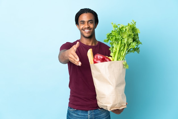 Uomo afroamericano che tiene un sacchetto della spesa della drogheria isolato su priorità bassa blu che agita le mani per chiudere un buon affare
