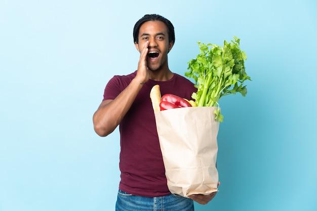 Uomo afroamericano che tiene un sacchetto della spesa isolato su priorità bassa blu che grida con la bocca spalancata