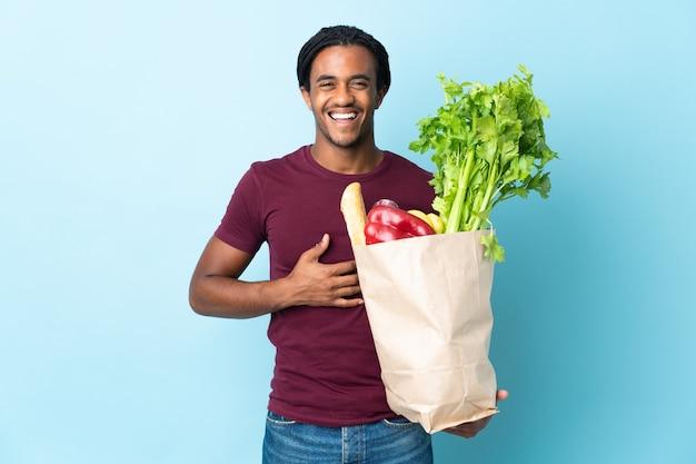 Uomo afroamericano che tiene un sacchetto della spesa della drogheria isolato su priorità bassa blu che sorride molto
