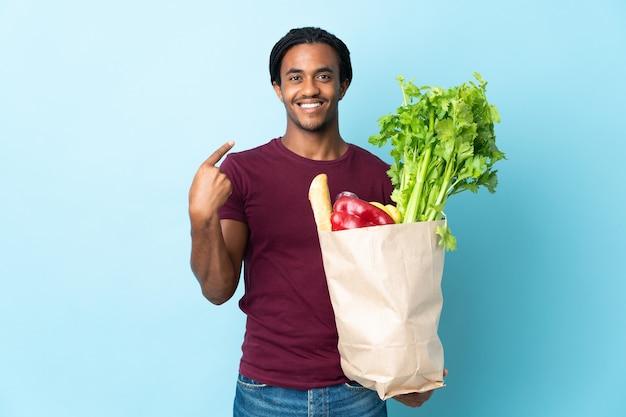 Uomo afroamericano che tiene un sacchetto della spesa della drogheria isolato su priorità bassa blu con l'espressione facciale di sorpresa