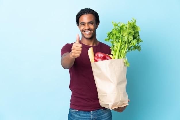 Uomo afroamericano che tiene un sacchetto della spesa isolato su priorità bassa blu con i pollici in su perché è successo qualcosa di buono