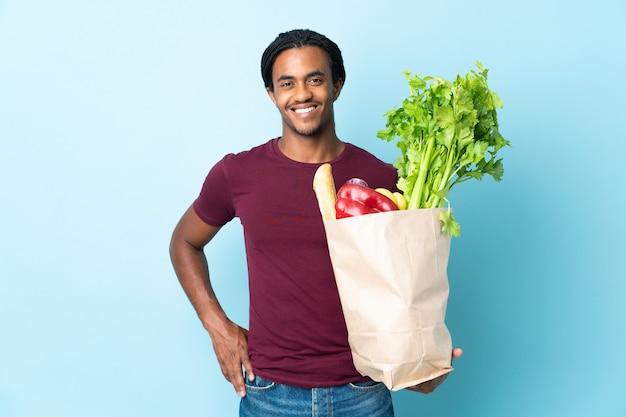 Uomo afroamericano che tiene un sacchetto della spesa della drogheria isolato sulla posa blu con le braccia all'anca e sorridente