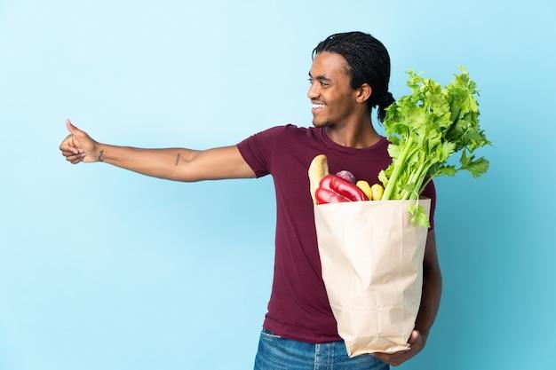 L'uomo afroamericano che tiene un sacchetto della spesa della drogheria isolato sulla parete blu che dà i pollici aumenta il gesto