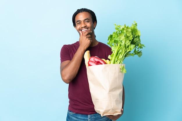 Uomo afroamericano che tiene un sacchetto della spesa della drogheria isolato sulla parete blu felice e sorridente