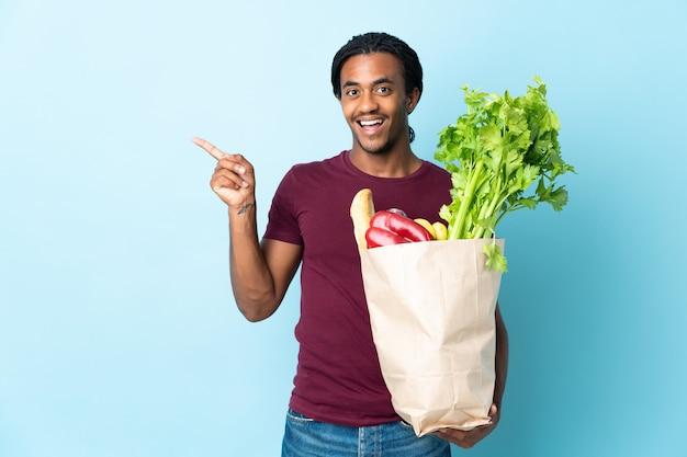 L'uomo afroamericano che tiene una borsa della spesa isolata sulla parete blu che intende realizzare la soluzione mentre solleva un dito