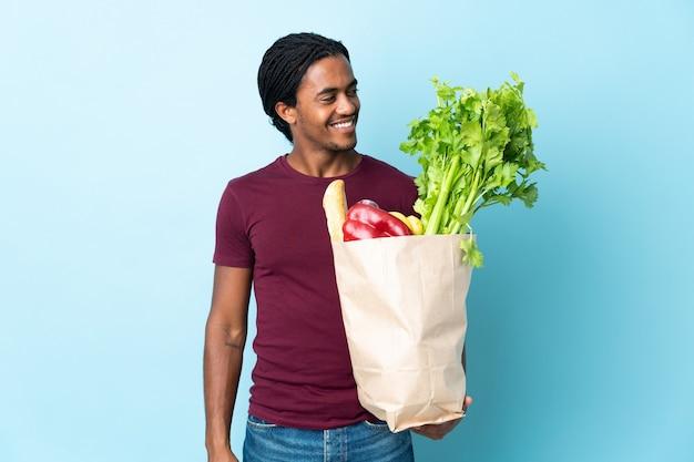 Uomo afroamericano che tiene un sacchetto della spesa della drogheria isolato sulla parete blu che osserva al lato e che sorride