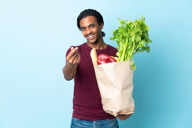 Uomo afroamericano che tiene un sacchetto della spesa della drogheria isolato sulla parete blu che fa gesto dei soldi