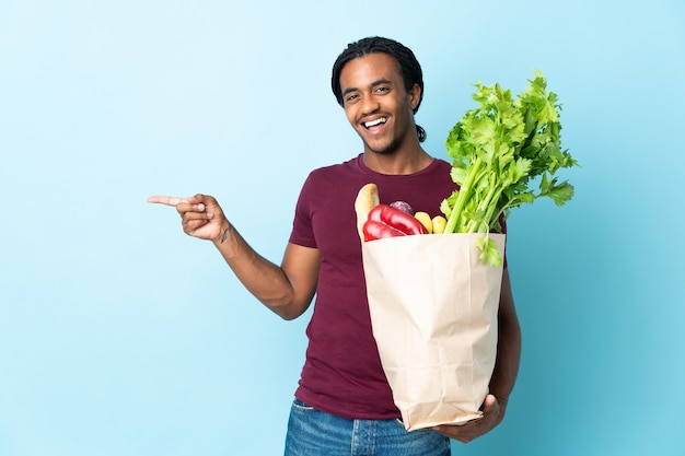 Uomo afroamericano che tiene un sacchetto della spesa della drogheria isolato sulla parete blu che indica il dito di lato e che presenta un prodotto