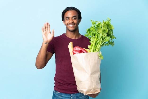 Uomo afroamericano che tiene un sacchetto della spesa della drogheria isolato sulla parete blu che saluta con la mano con l'espressione felice