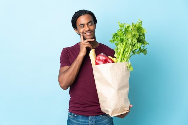 Uomo afroamericano che tiene una borsa della spesa isolata sulla parete blu che pensa un'idea mentre osserva in su