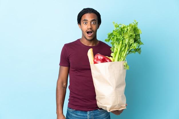 Uomo afroamericano che tiene un sacchetto della spesa della drogheria isolato sulla parete blu con l'espressione facciale di sorpresa