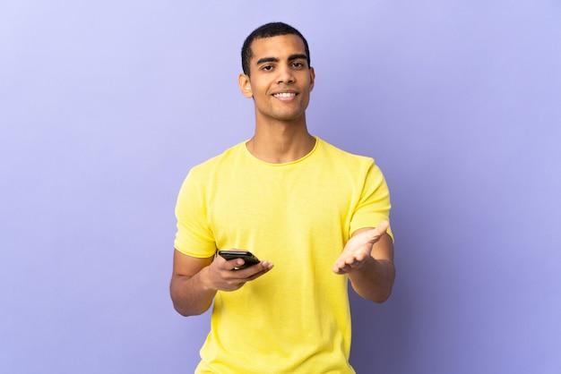 Uomo afroamericano su viola isolato utilizzando l'handshaking del telefono cellulare dopo un buon affare