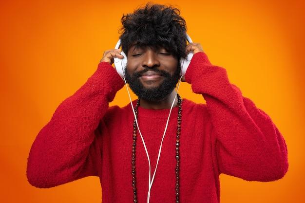 Uomo afroamericano che ascolta con gioia musica su sfondo arancione orange